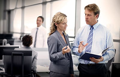 Two Business People Standing Discussing Document