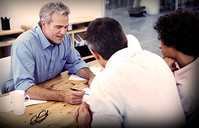 Business Casual Man Explaining Document to Couple