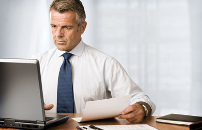 Businessman at Desk with Computer and Paperwork
