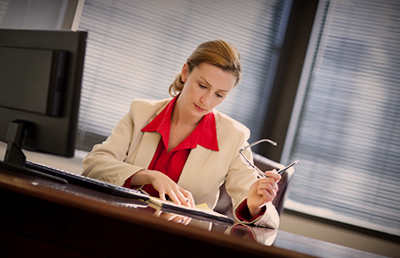 Business woman Desk Monitor Reviewing Papers