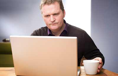 Man at Computer Looking Puzzled