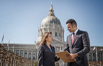 Two-Businesspeople-Standing-in-Front-of-Capitol-Building