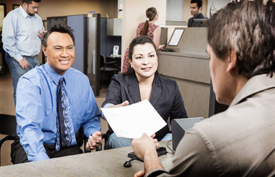 Couple-Handing-Paperwork-to-Bank-Employee Uniform Residential Loan Application on new enhancements, sample data, already filled, rural development, example completed, clip art, freddie mac form,